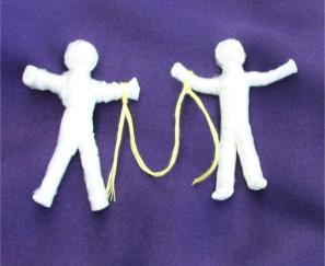 Friendship poppets tied with yellow string